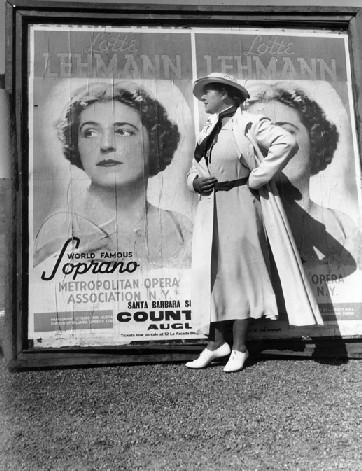 Lotte Lehmann stands next to a concert poster