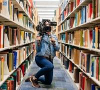 woman holding video camera behind stacks